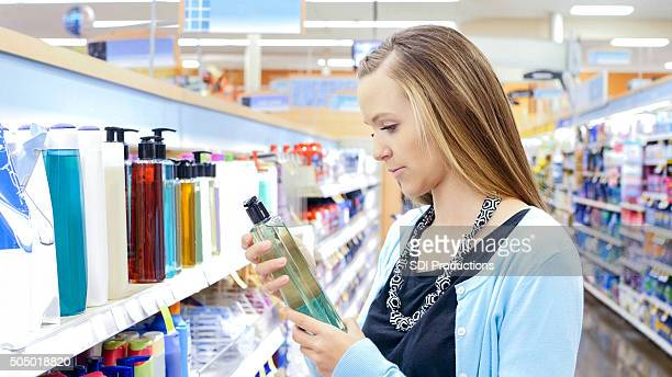 Young woman shopping for shampoo and beauty products in store
