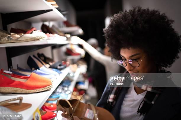 young woman shopping for shoes - ver a hora imagens e fotografias de stock