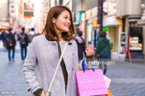 Young woman shopping in a busy Japanese city