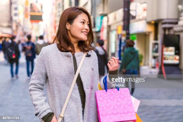 若い女性が日本の都会でのショッピング