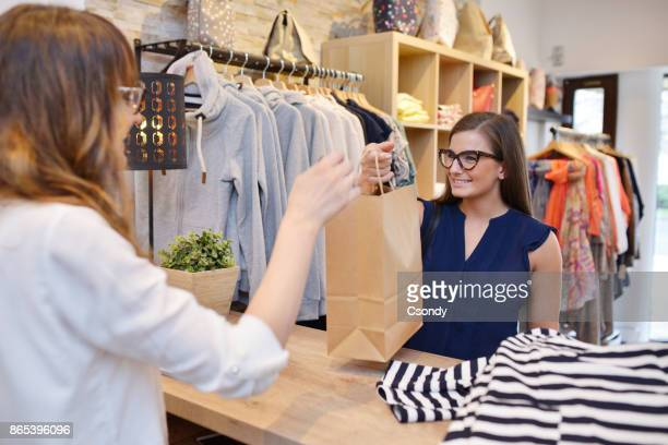 young woman shopping in a fashion store - passing giving stock photos and pictures