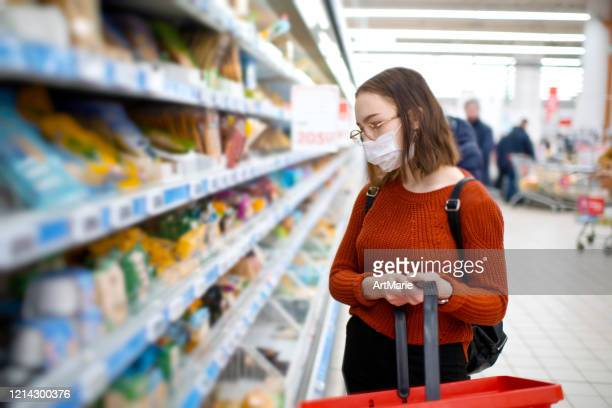 young woman shopping in a grocery store and wearing protective medical mask - consumerism stock pictures, royalty-free photos & images