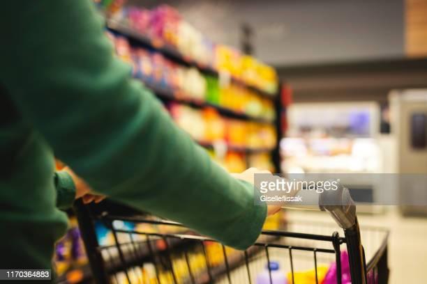 compra da mulher nova em um supermercado - consumismo - fotografias e filmes do acervo