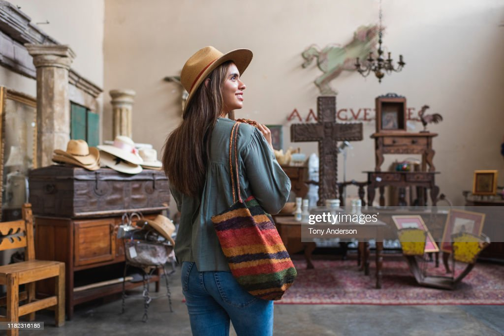Young woman shopping in antique store : Stockfoto