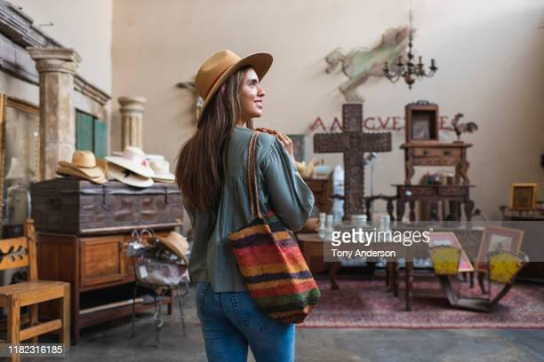 young woman shopping in antique store - nosotroscollection stock pictures, royalty-free photos & images