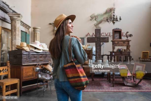 young woman shopping in antique store - nosotroscollection stockfoto's en -beelden