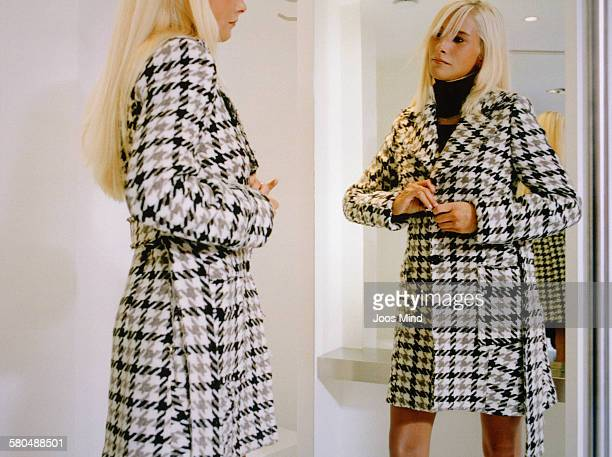 young woman shopping in clothes store - overcoat stock pictures, royalty-free photos & images