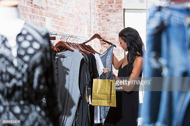 若い女性ファッションストアでショッピング