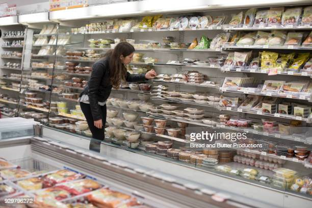 young woman shopping in convenience store - convenience store stock pictures, royalty-free photos & images