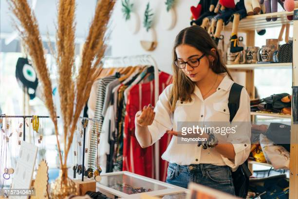 young woman shopping in second hand marketplace - flea market stock pictures, royalty-free photos & images