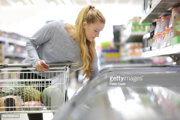 young woman shopping in supermarket - frozen food stock pictures, royalty-free photos & images