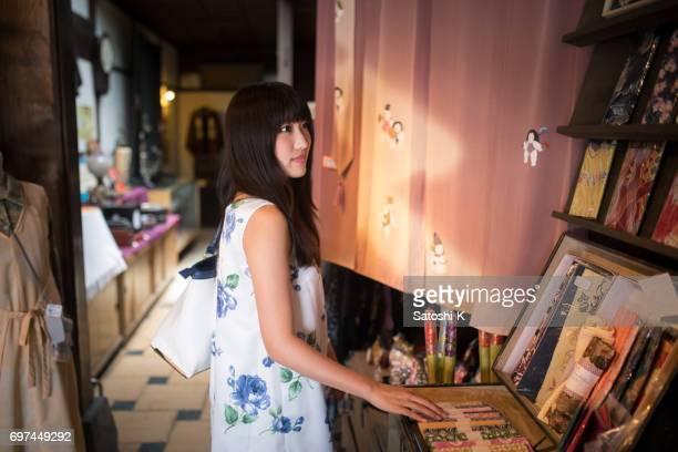 Junge Frau, die in traditionellen japanischen Ladengeschäft einkaufen