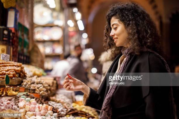 jeune femme, faire du shopping dans la boutique délice turc dans le grand bazar, istanbul, turquie - bonne fete de ramadan photos et images de collection