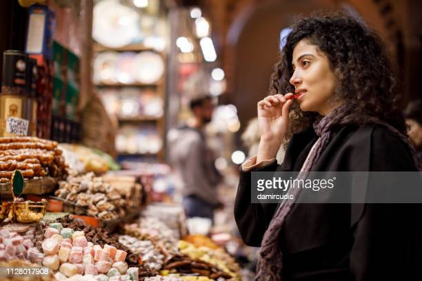 young woman shopping in turkish delight shop in grand bazaar, istanbul, turkey - middle east stock pictures, royalty-free photos & images