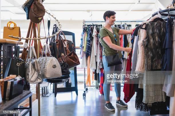 young woman shopping in vintage boutique - bisexuality fotografías e imágenes de stock