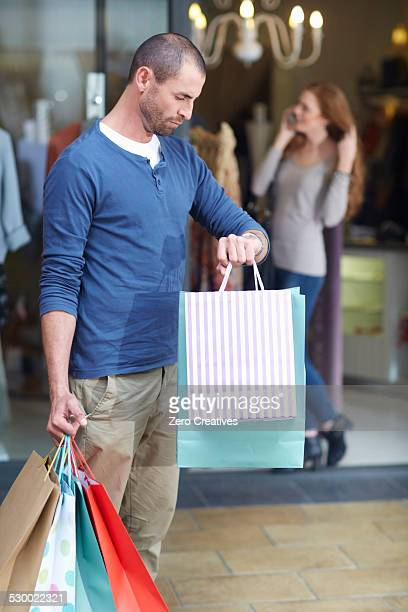 Young woman shopping, man outside holding bags, looking at watch