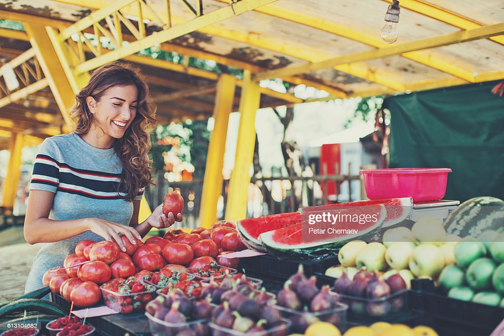 Young woman shopping on the farmer's market : Stock Photo