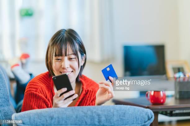 若い女性が自宅のオンライン ショッピング - オンラインショッピング ストックフォトと画像