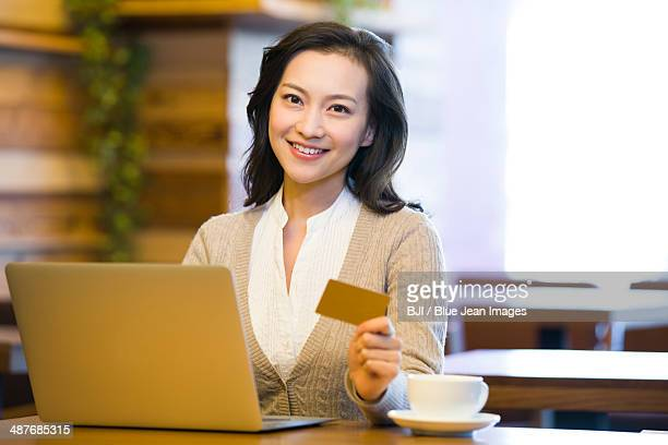 Young woman shopping online in cafe