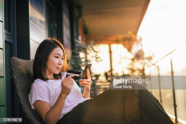 young woman shopping online with smart phone and credit card - buying stock pictures, royalty-free photos & images