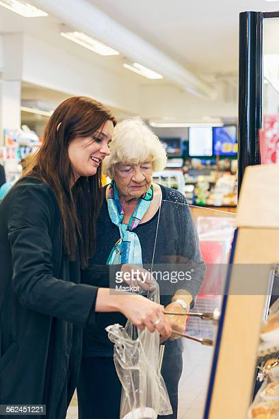 Young woman shopping with grandmother at supermarket