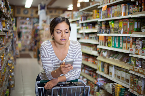 Young woman shopping with smartphone in health food store - gettyimageskorea