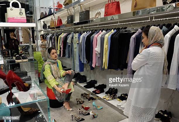 A young woman shops for famous international brand high heel shoes in the newly opened Palladium shopping mall on April 28 2016 in Tehran Iran...