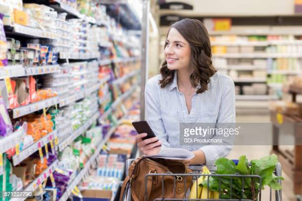 Young woman shops in dairy section of grocery store