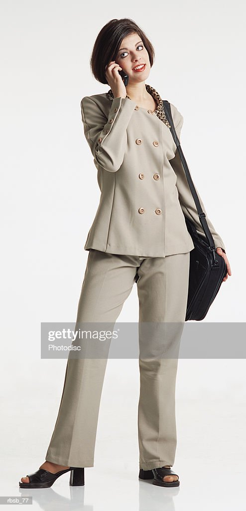 young woman short dark hair wears tan suit briefcase over shoulder looks away talking on cell phone : Foto de stock