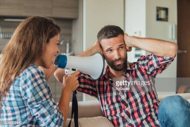 Young woman shouting at the man through megaphone