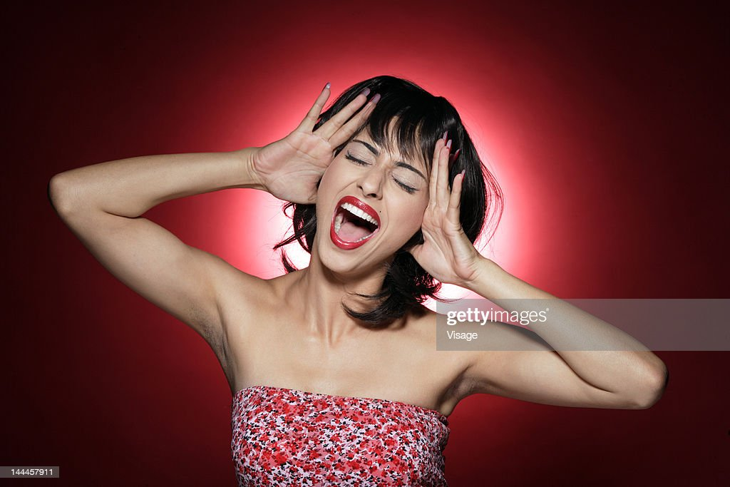Young woman shouting, hands on head : Stock Photo