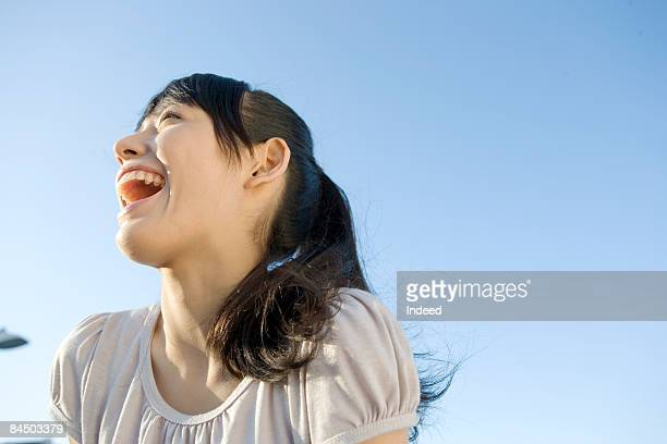Young woman shouting, low angle view