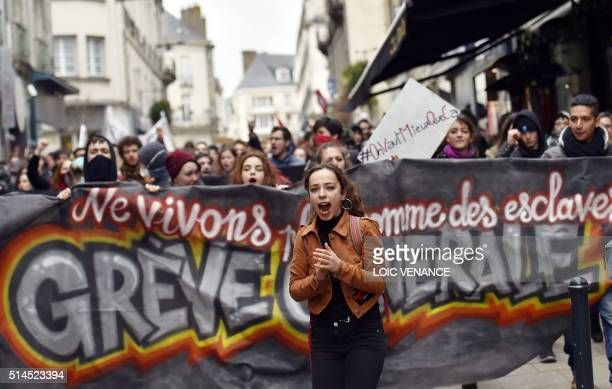 TOPSHOT A young woman shouts slogans in front of a banner as thousands of people demonstrate on March 9 2016 in Nantes western France as part a...
