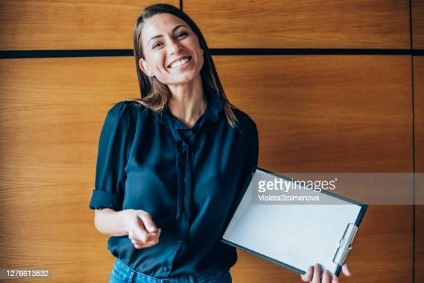 young woman showing a blank paper page. - promoter stock pictures, royalty-free photos & images