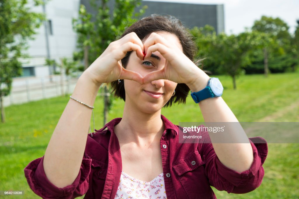 Young woman showing a heart-shape symbol with hands : Stock Photo