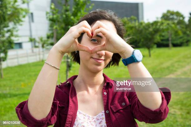 young woman showing a heart-shape symbol with hands - high school musical: the musical: the series stock photos and pictures