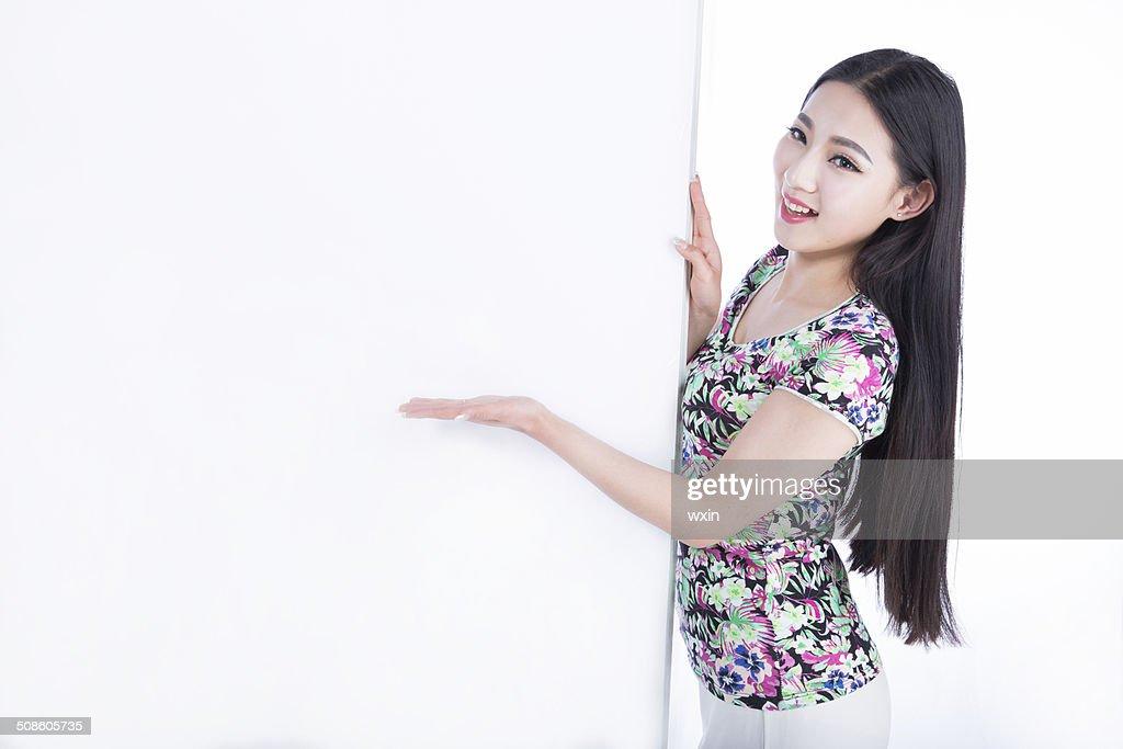 Jovem mulher mostrando em branco Pintura, isolado em fundo branco : Foto de stock