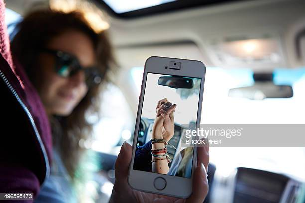 young woman showing cell phone photo - holding hands in car stockfoto's en -beelden