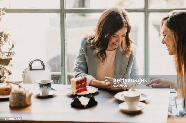 young woman showing cell phone to friend in a cafe - female friendship stock pictures, royalty-free photos & images