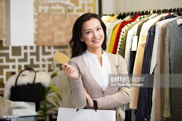Young woman showing credit card in clothing store