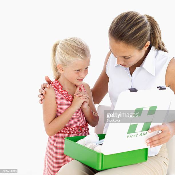 young woman showing her daughter a first aid kit - kids first aid kit stock pictures, royalty-free photos & images