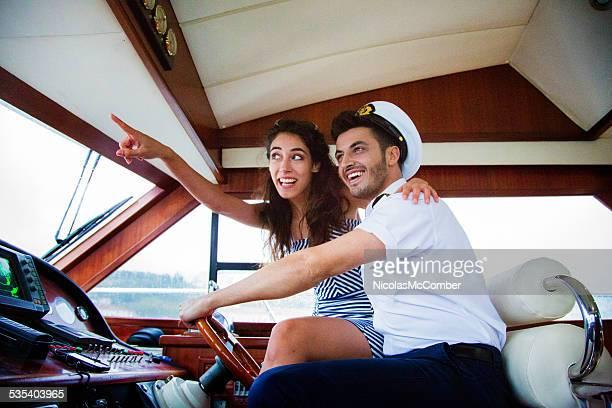 若い女性は彼女のヨットで、船長を表示する - セーラーハット ストックフォトと画像