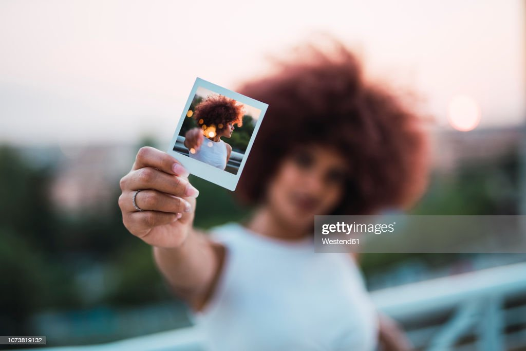 Young woman showing instant photo of herself, close-up : Stock Photo