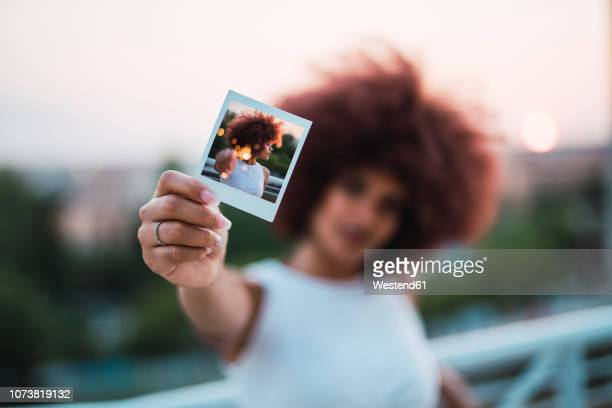 young woman showing instant photo of herself, close-up - blick in die kamera stock-fotos und bilder