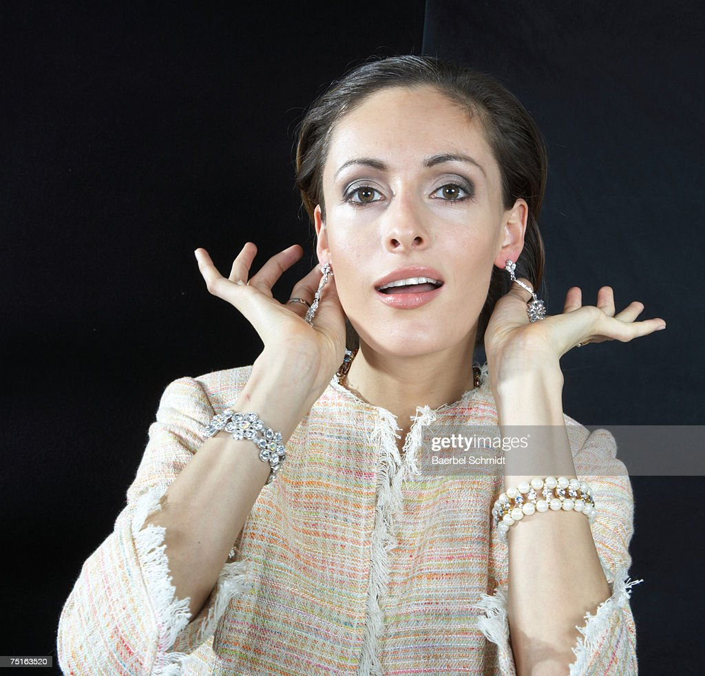 Young woman showing off earrings : Stock Photo