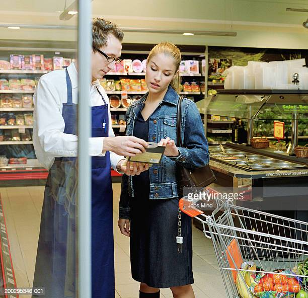 Young woman showing packet to supermarket assistant