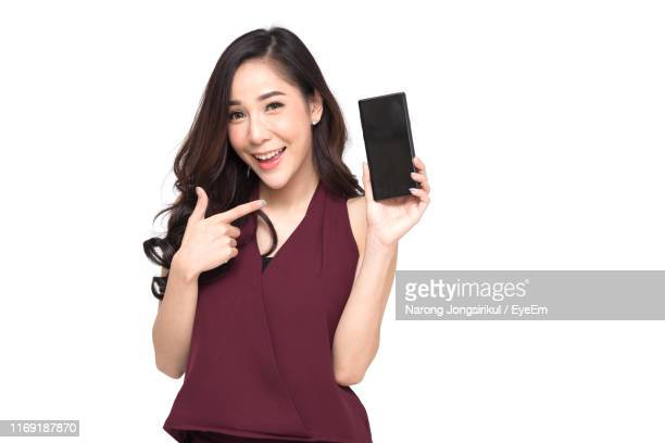 young woman showing phone while standing against white background - 見せる ストックフォトと画像
