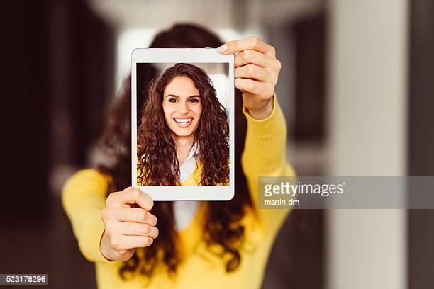 Jeune femme montrant des autophotos sur une tablette pc