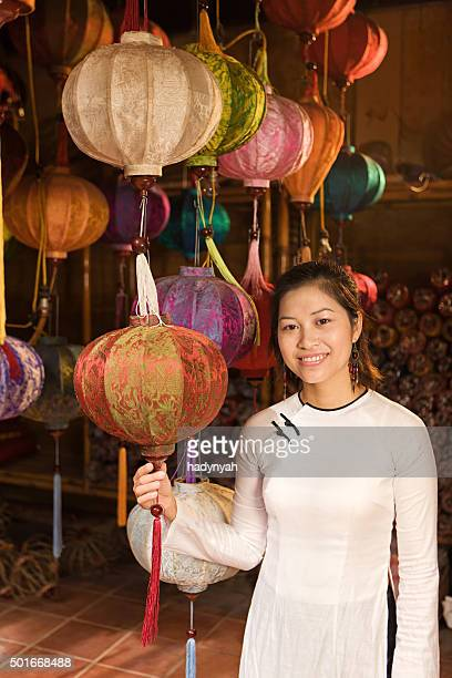Young woman showing silk lanterns in Hoi An city, Vietnam