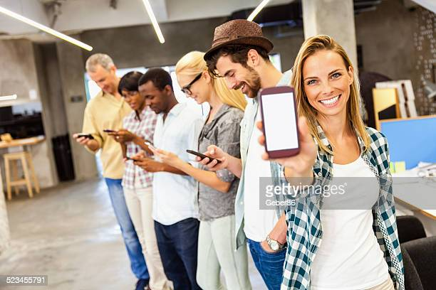 Young woman showing smart phone